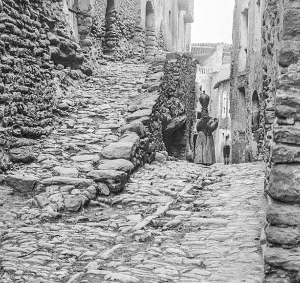 Carrer del poble d'Àger amb una dona portant un càntir al cap (any 1890). Autor: Frederic Bordas i Altarriba. Fons: Centre Excursionista de Catalunya.